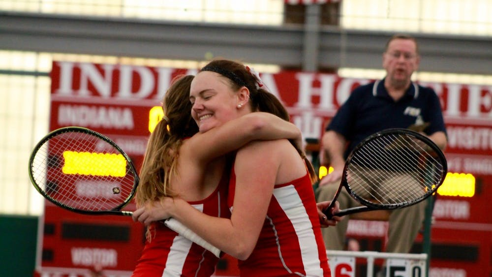 Then-sophomores Caitlin Bernard and Natalie Whalen celebrate after defeating their opponents in a doubles match Feb. 18, 2017. IU lost to Ohio State on Sunday, 6-1.