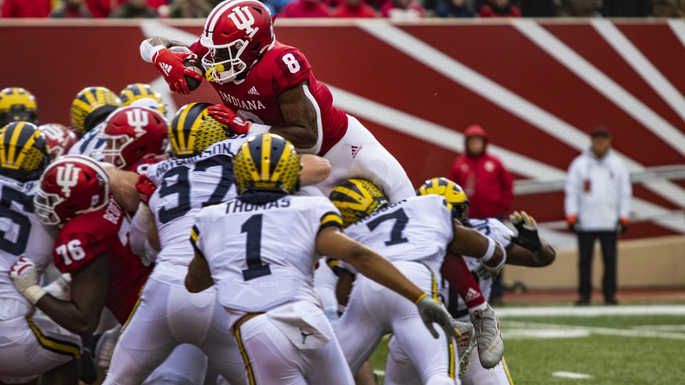 Sophomore running back Stevie Scott III attempts to jump over Michigan's defensive linemen with the ball Nov. 23 in Memorial Stadium. Scott scored IU's first touchdown.
