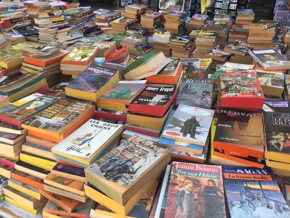 A table of stacked books sit in Book Corner on Kirkwood Avenue.