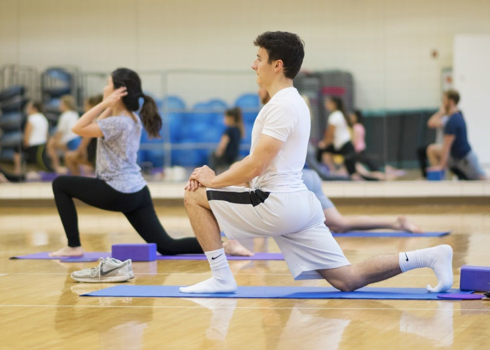 <p>Junior Zach Geremia stretches in a yoga pose at the Bro Flow Yoga-60 session on Oct. 4. Men and women can participate in the yoga practice, which is geared towards athletes.&nbsp;</p>