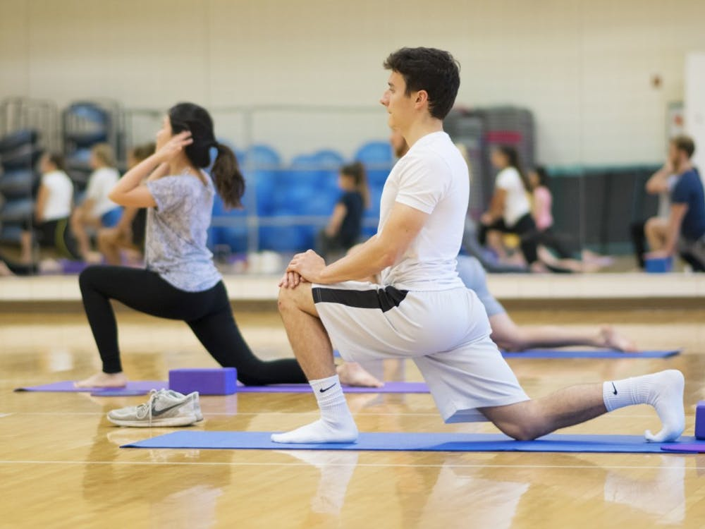 Junior Zach Geremia stretches in a yoga pose at the Bro Flow Yoga-60 session on Oct. 4. Men and women can participate in the yoga practice, which is geared towards athletes.