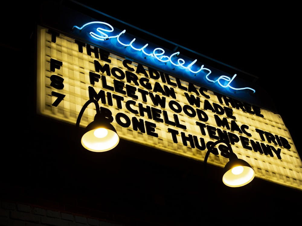 A sign is lit up for the Cadillac Three Jan. 30, 2020, outside the Bluebird. The Bluebird temporarily shut down Thursday to create a plan for COVID-19 safety and compliance.