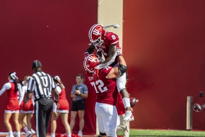 Fifth-year offensive lineman Simon Stepaniak lifts sophomore running back Stevie Scott III on Sept. 21 at Memorial Stadium. Scott scored the final touchdown in the fourth quarter.