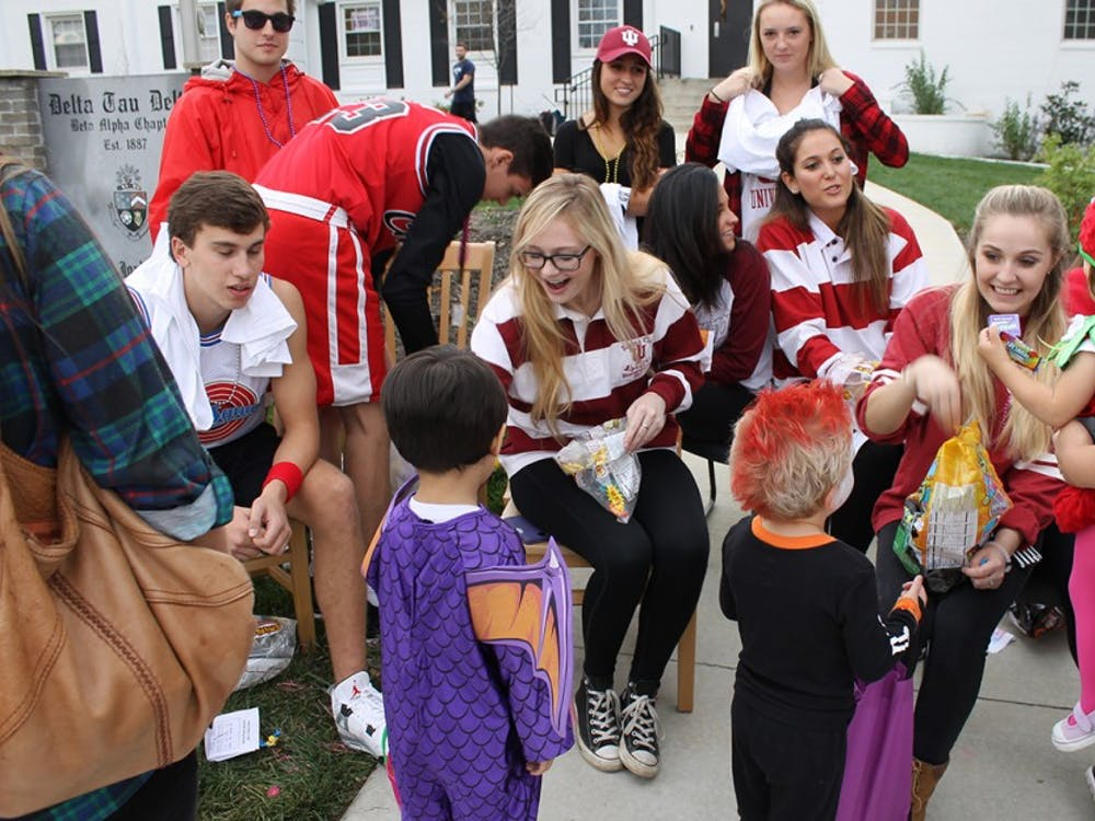 Students pass out candy to children in front of the Delta Tau Delta fraternity house on Wednesday.