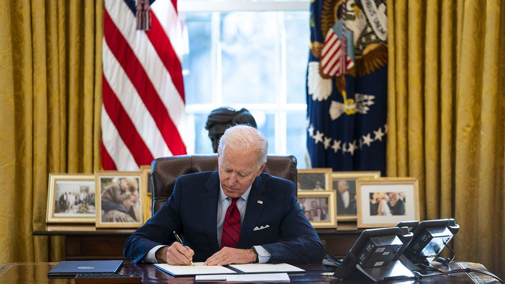 President Joe Biden signs an executive order combatting xenophobia toward Asian-Americans and Pacific Islanders on Jan. 26 in the Oval Office. Part of the executive order includes a requirement that the Department of Justice must increase the collection of hate crime incident reports.