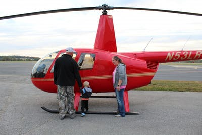 Ellettsville residents Katie, Robert and their son Jaxson Jones view a helicopter Oct. 19 at the Monroe County Airport. Community Flight Night allowed residents to view planes, ride in a hot air balloon and tour the airport.