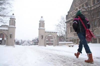 A student makes her way down a snow-covered path through the Sample Gates.