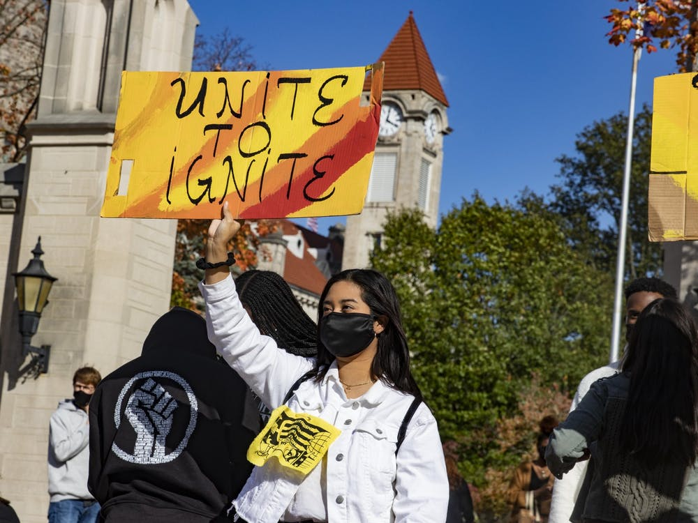 "Junior Evelyn Sanchez holds up a sign that reads, ""Unite to ignite,"" during the Unite To Ignite rally Oct. 16 in front of Sample Gates. ""Multicultural students don't get much representation in IUSG,"" she said."