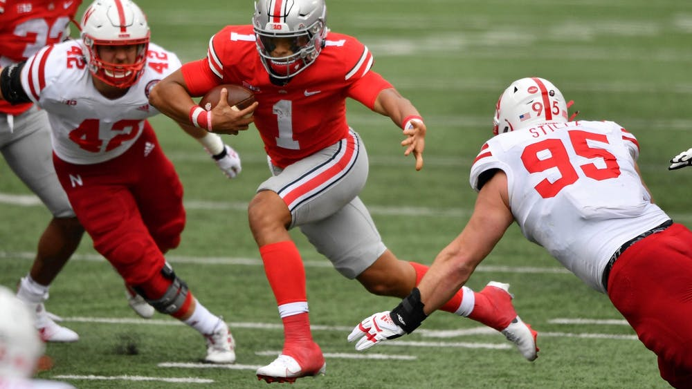 Ohio State quarterback Justin Fields picks up yardage in the second quarter as Nebraska defends Saturday at Ohio Stadium in Columbus, Ohio. The Buckeyes beat the Cornhuskers 52-17.