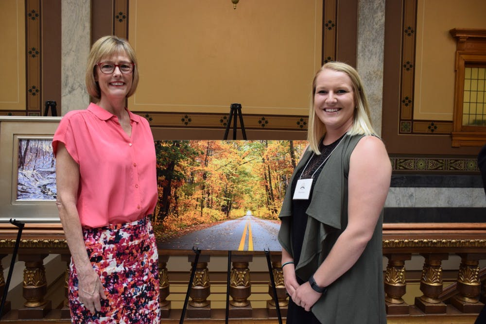 """<p>Artist Alina Davis poses with one of her works, titled """"The Yellow Brick Road,"""" at a previous Hoosier Women Artists Contest. Submissions for the 2018 Hoosier Women Artists Contest are due Friday, Jan. 26.</p>"""