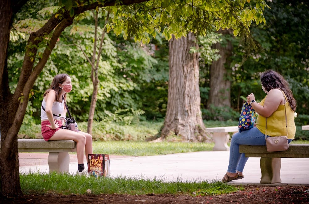 <p>Sophomores Yatziri Moreno, left, and Meg Heinisch, right, meet Aug. 24 behind Bryan Hall. Monroe County will maintain its COVID-19 social gathering restrictions and mask mandates even though Gov. Eric Holcomb announced earlier this week he will end the statewide mask mandate on April 6, Mayor John Hamilton said in Bloomington's weekly COVID-19 press conference Friday.</p>