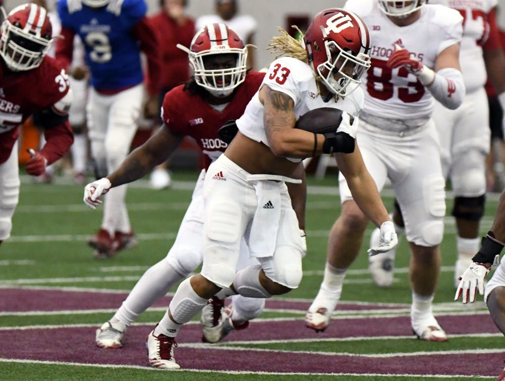 <p>Redshirt senior running back Ricky Brookins runs the ball during the IU spring game Saturday in Mellencamp Pavilion. The crimson team won the game, 37-28.</p>