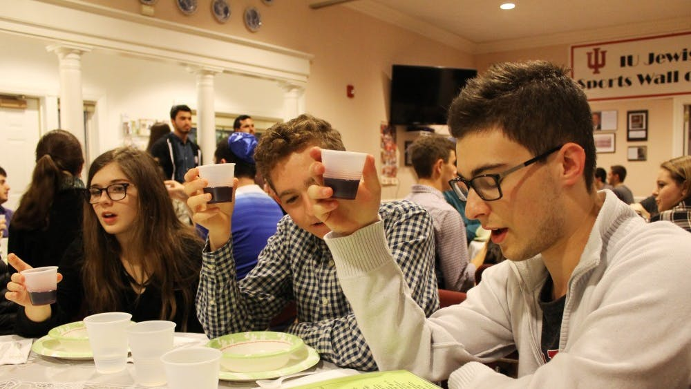 IU students Olivia Turi, Evan Weis and Max Gruenberg raise cups of grape juice during a pre-meal blessing in January 2017 at the Helene G. Simon Hillel Canter. Hillel is one of the many religious organizations on campus.