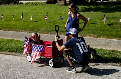 Bloomington resident Kyle Canid takes a photograph of his two-year-old, Quinn, on July 4 on East Arden Drive. The 58th annual Arden Place Neighborhood parade took place with safety precaution alterations due to the pandemic.