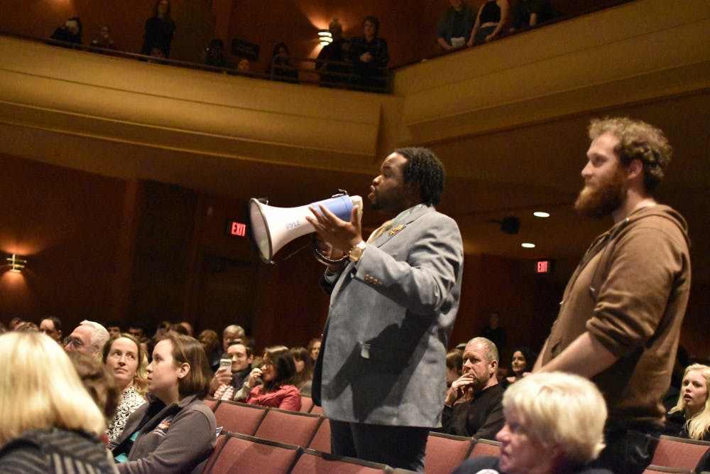 <p>Vauhxx Booker and Steven Dora use a megaphone to protest the recent purchase of an armored truck by the Bloomington Police Department. The protest took place during Thursday's State of the City Address, and led to the early adjournment of the special session.</p>
