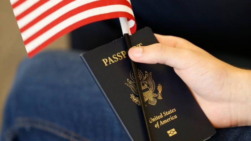 A hand holds a passport. Long visa approval wait times can cause IU students to miss the start dates of their internships and classes.
