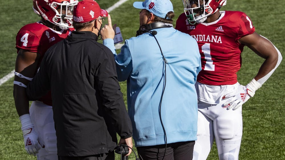 Head coach Tom Allen and defensive coordinator Kane Wommack talk to junior defensive back Devon Matthews and junior linebacker Cam Jones on Oct. 24 in Memorial Stadium. Wommack has been hired as the head coach at the University of South Alabama.