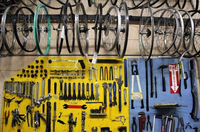 Bicycle wheels hang above repair tools Sept. 16 at the Bloomington Community Bike Project. IU Surplus made a donation of roughly 40 bikes and bike parts to the Bloomington Community Bike Project after receiving bikes from IU Parking Operations the first week of September.