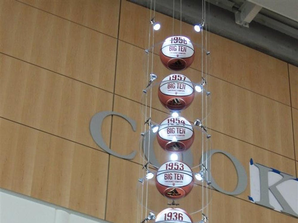 """Seven of the basketballs in Cook Hall commemorating IU's Big Ten Championships, as the finishing touches are put onto the """"Cook Hall"""" lettering on the wall of Pfau Shine Legacy Court."""