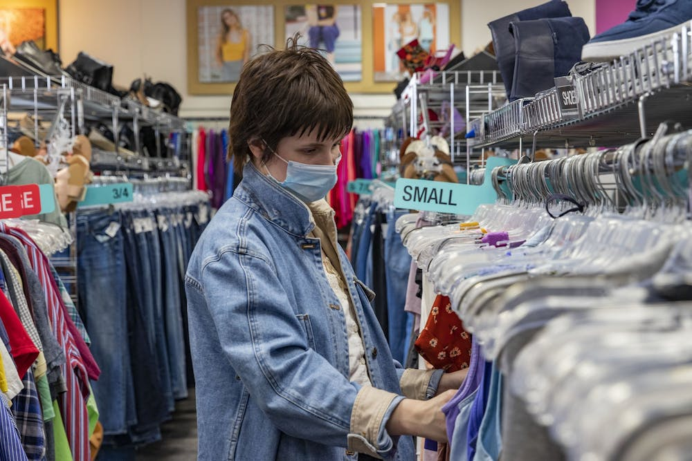 """<p>20-year-old Katie Hohman looks at tank tops Monday in Plato's Closet in Bloomington. """"I'm looking at cute tops for the summer,"""" she said.</p>"""