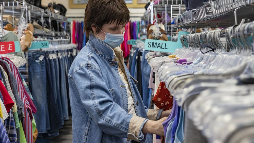 """20-year-old Katie Hohman looks at tank tops Monday in Plato's Closet in Bloomington. """"I'm looking at cute tops for the summer,"""" she said."""