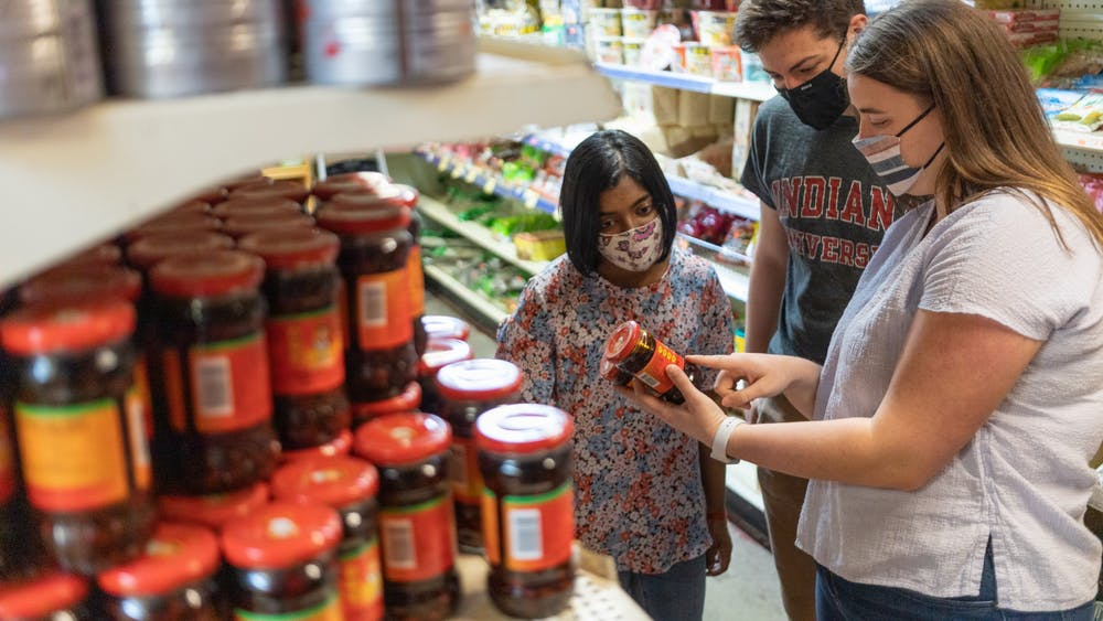 Shreya Mapadath, Ethan Joss and Marria Peduto shop for food March 24 at B-Town International Market. The three IU students distribute food boxes to other students and organize discussions about food insecurity.
