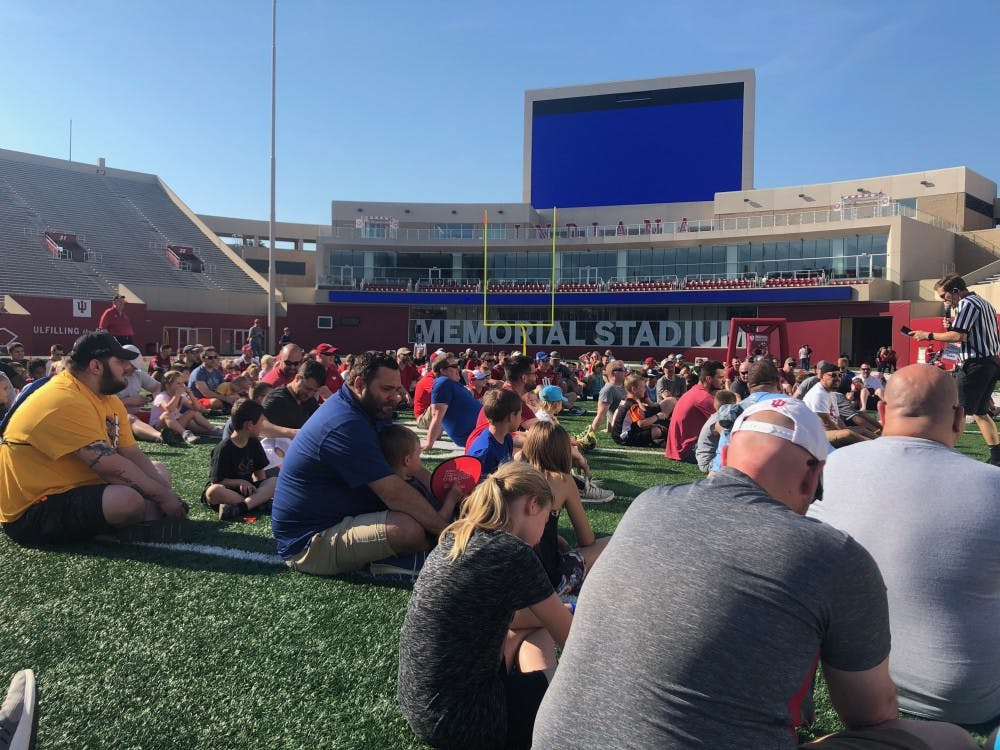<p>Children and fathers listen intently to IU Football Coach Tom Allen during the opening address of the All Pro Dad Experience on Saturday at Memorial Stadium.</p>