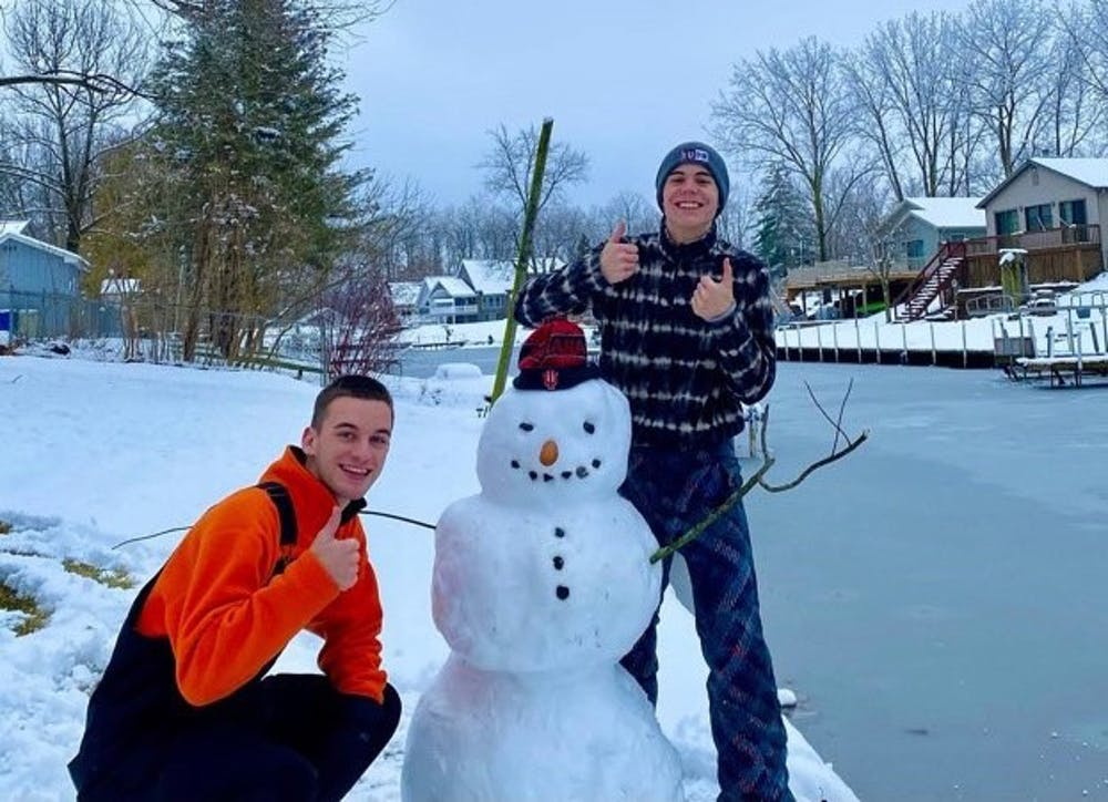 <p>Sophomore Carson Conrad and his friend pose with their snowman, whose nose is a corndog.</p>