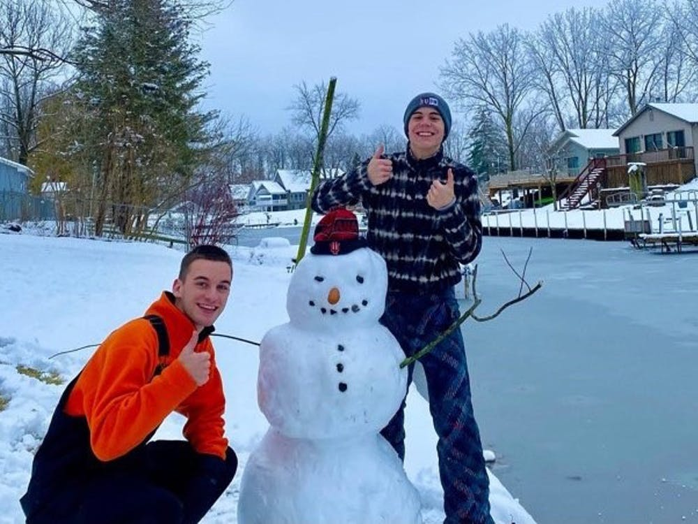 Sophomore Carson Conrad and his friend pose with their snowman, whose nose is a corndog.