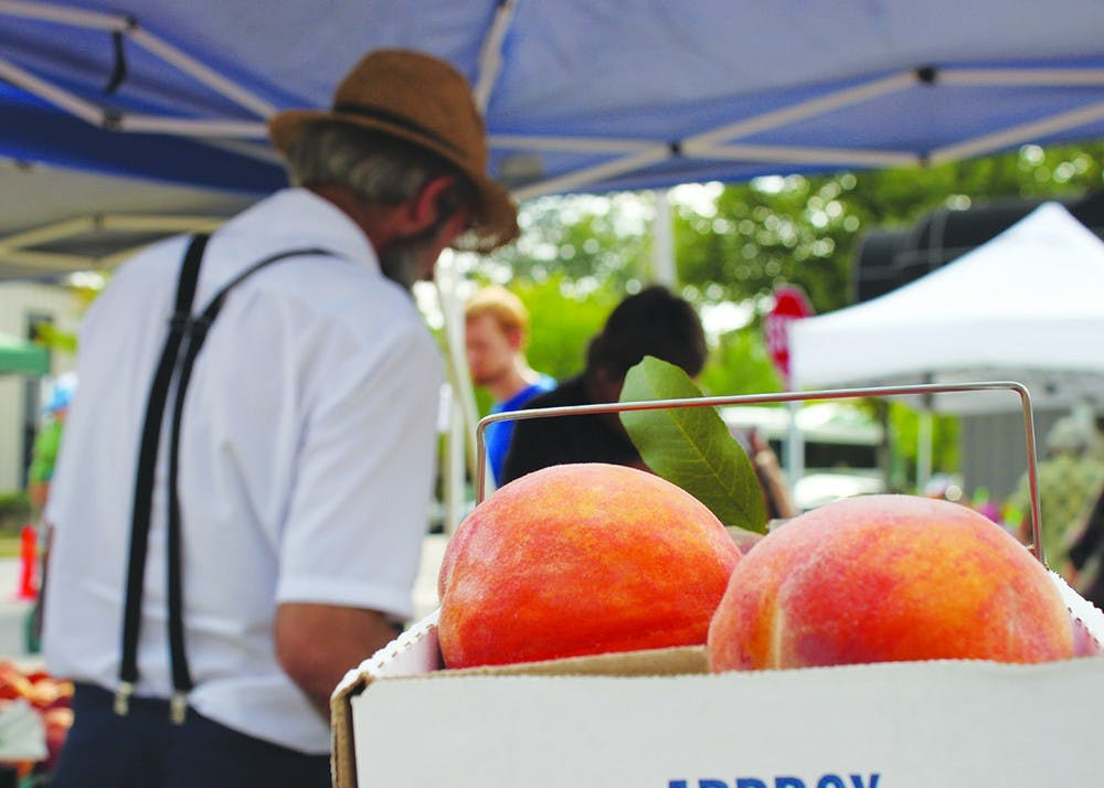 <p>Daniel Graber sells fruit at the Bloomington Farmers' Market in 2013 in front of a box of peaches, his main crop. The city's director of economic and sustainability development discussed the city's solar energy initiative at Saturday's market.</p>