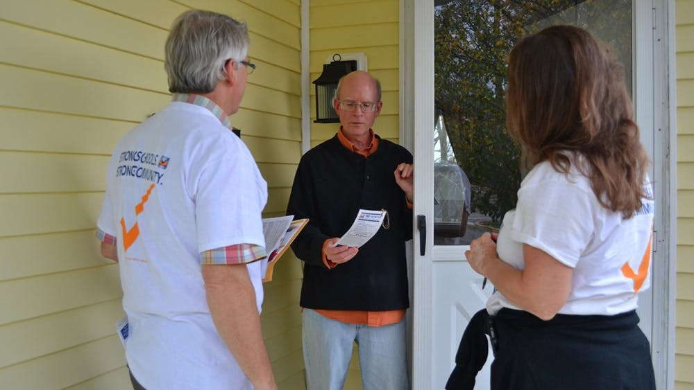 Mayor John Hamilton and schoolboard candidate Cathy Fuentes-Rohwer canvas and talk to voters about the referendum Wednesday night.