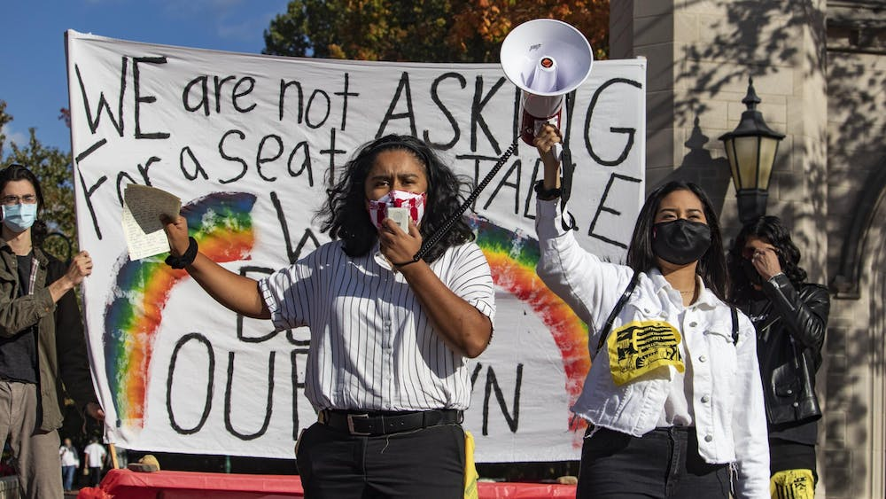 Senior Ruby Flores Camacho and junior Evelyn Sanchez stand together and give a speech during the Unite To Ignite rally Oct. 16 in front of the Sample Gates.