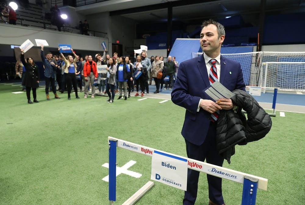 <p>Caucus participant Jarad Bernstein supports former Vice President Joe Biden on Feb. 3 by standing behind a track and field hurdle bearing Biden&#x27;s name in Des Moines, Iowa.</p>