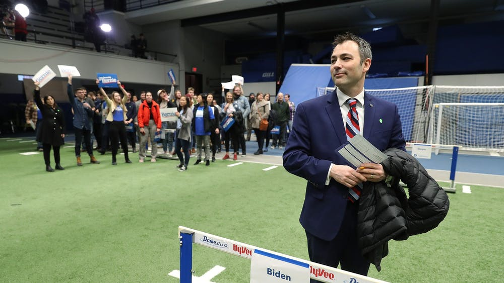 Caucus participant Jarad Bernstein supports former Vice President Joe Biden on Feb. 3 by standing behind a track and field hurdle bearing Biden's name in Des Moines, Iowa.