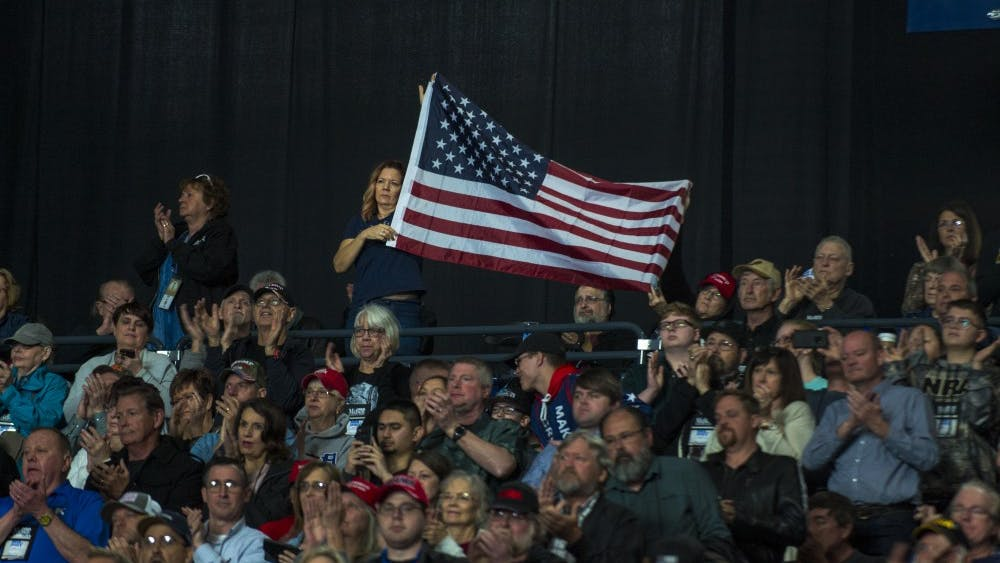 A woman holds an American flag while Vice President Mike Pence speaks April 26 at the NRA-ILA Leadership Forum in Lucas Oil Stadium in Indianapolis.