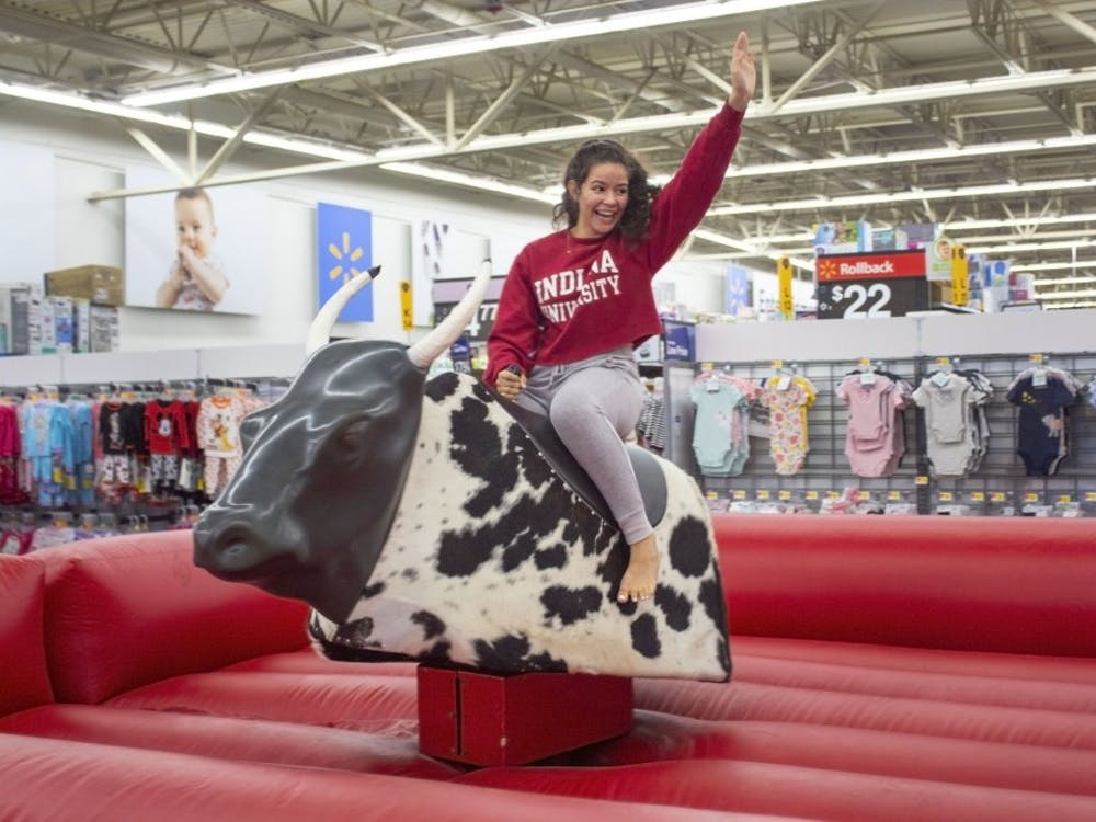 IU senior Abir Ouzzine rides a mechanical bull Aug. 22 at the Office of First Year Experience Program's Midnight Madness event. This year's event was at Walmart and featured many activities, including a giant Twister game and a dance floor.