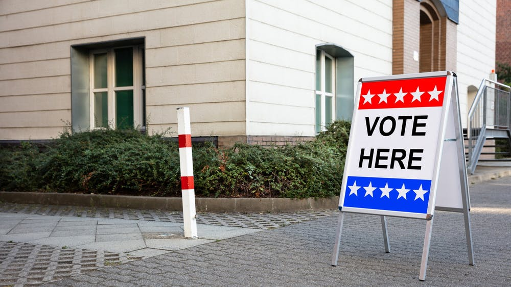 """A sign that reads """"vote here"""" is seen outside a polling place in Miami-Dade County in Florida."""