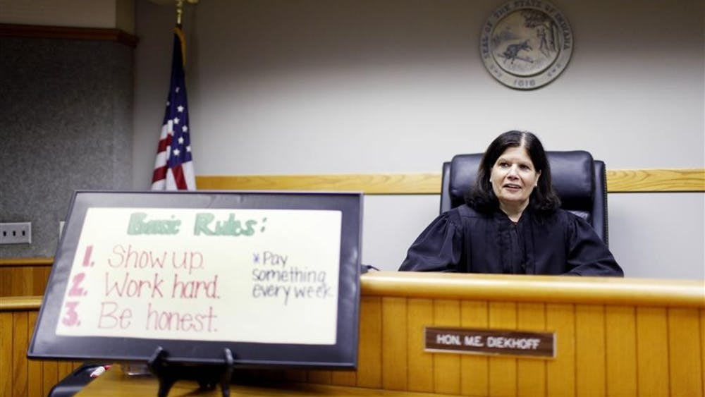 Judge Mary Ellen Diekhoff laughs as she and a case manager tease one another while she sits for a portrait on April 21, 2014, at the Monroe County Justice Building.