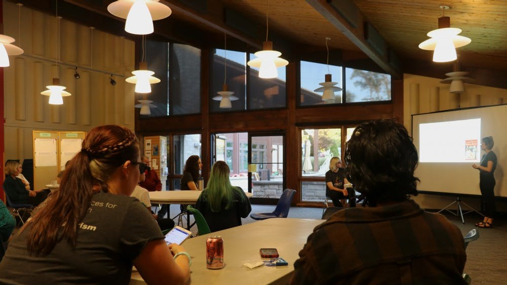 Bloomington community members listen to a presentation on LGBTQ+ History given by Prism Youth Community leaders Tuesday evening. Prism Youth Community is a youth-lead initiative to promote inclusivity.