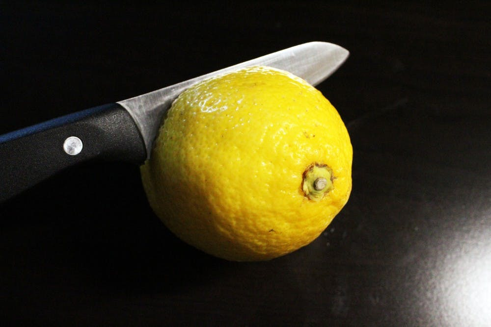 <p>A knife cuts through a lemon on a kitchen counter.</p>