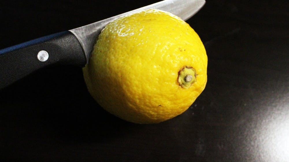 A knife cuts through a lemon on a kitchen counter.