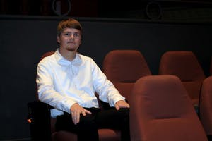 Sophomore Will Eltzroth sits in a designated usher seat in the back of the IU Cinema. Eltzroth set a record for the most volunteer shifts at the cinema since its opening in 2011, numbering 81 shifts in one year.