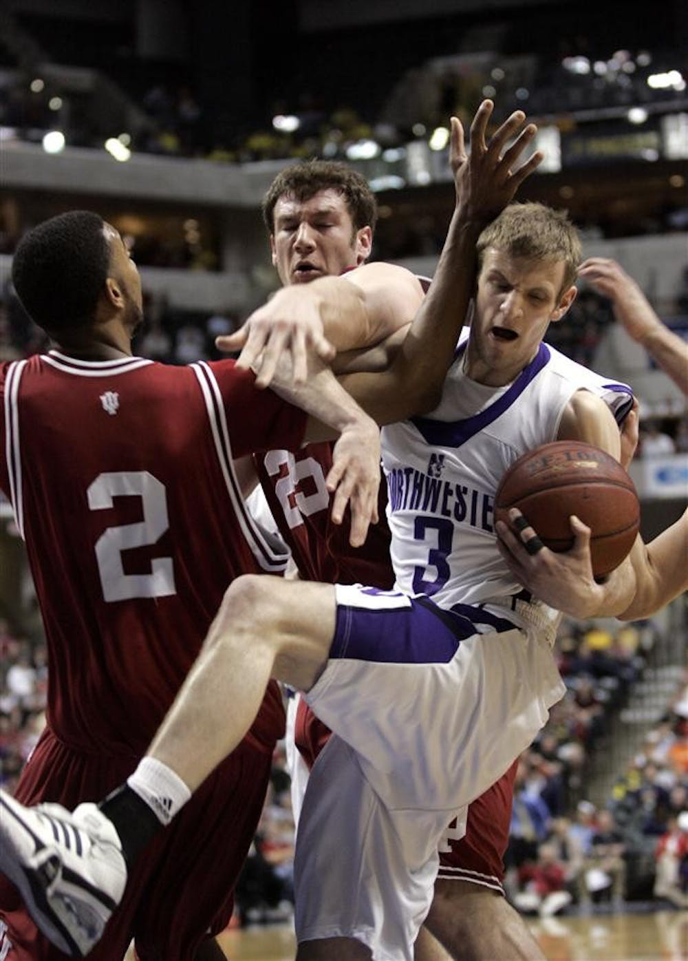The Hoosiers attempt to steal the ball from Northwestern's Mike Capocci Thursday night during the Big Ten Tournament at Conseco Fieldhouse in Indianapolis.