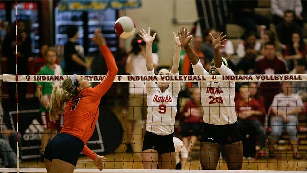 Junior setter Megan Tallman and senior blocker Awele Nwaeze block a spike from an Illinois player. The Hoosiers fell to the Fighting Illini 3-0 on Friday at University Gym.