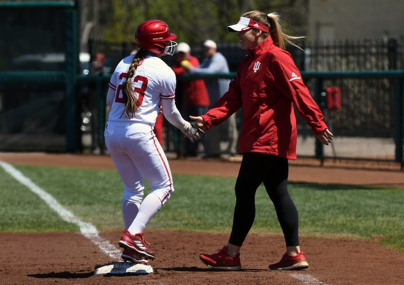 Sophomore utility player Gabbi Jenkins high-fives assistant coach Kendall Fearn during a game against Michigan in the 2018 season. Gwen Svekis was named a volunteer assistant coach for the Hoosiers on Monday.