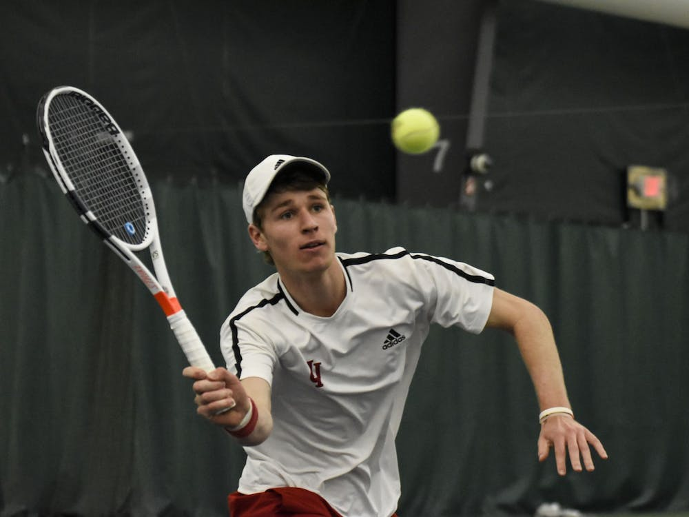 Then-sophomore Bennett Crane reaches for a forehand against Wisconsin on April 8, 2018, at IU Tennis Center. IU will play Wisconsin in the first round of the Big Ten Tournament.