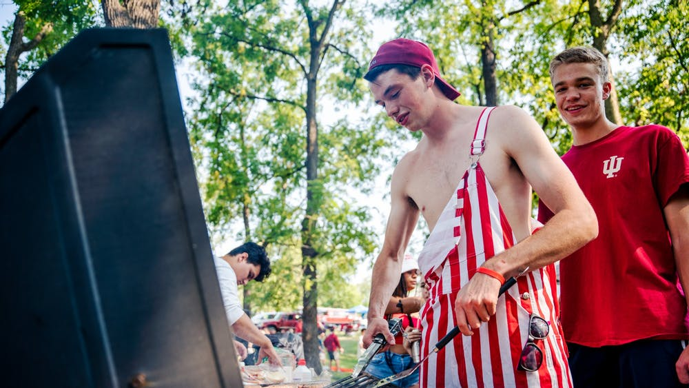 """Sophomore Steven Alton cooks hamburgers on a grill during his first tailgate before the Indiana home football game against the University of Idaho on Sept. 11, 2021, at the Indiana Tailgate Fields. """"I loved the energy and camaraderie amongst current, past, and future students,"""" Alton said. """"I couldn't have asked for a better way to kick off the year."""""""