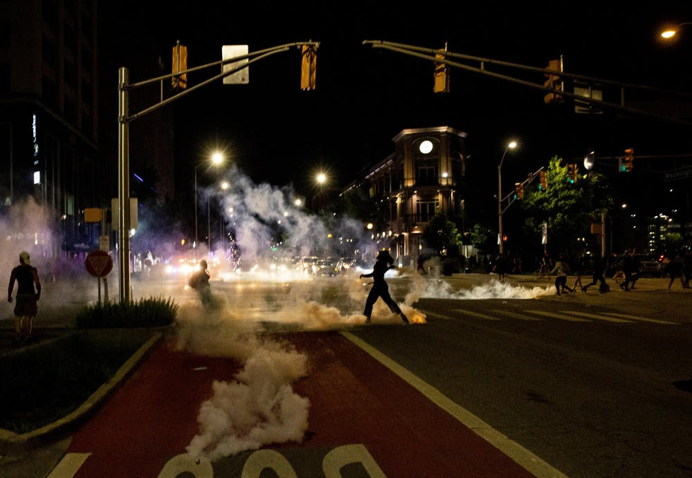 <p>Tear gas creeps up the street May 30 in Indianapolis. Police enforcement used tear gas to break up the protest in response to the police killings of George Floyd in Minneapolis, Breonna Taylor in Louisville, Kentucky, and Dreasjon Reed in Indianapolis.</p>