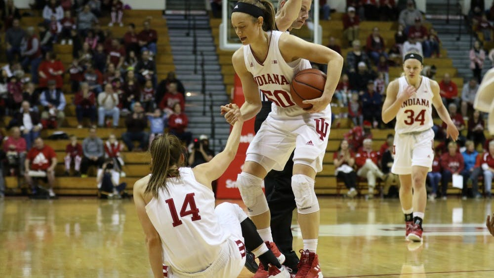 Junior Brenna Wise helps fellow junior Ali Patberg off the ground following a foul during the game against Missouri State on Dec. 9 at Simon Skjodt Assembly Hall.