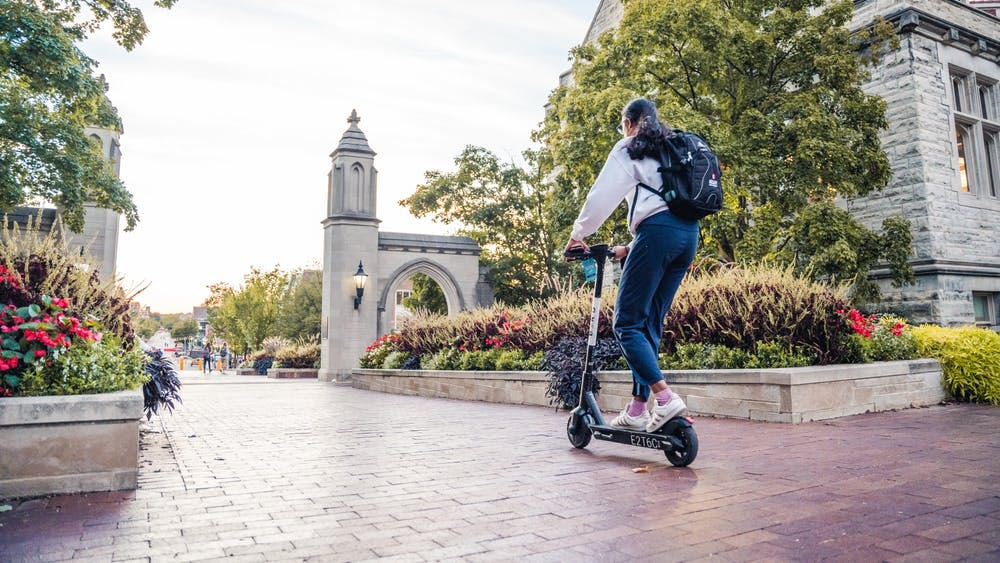 A woman rides an electric scooter Sept. 26, 2021, toward Sample Gates.